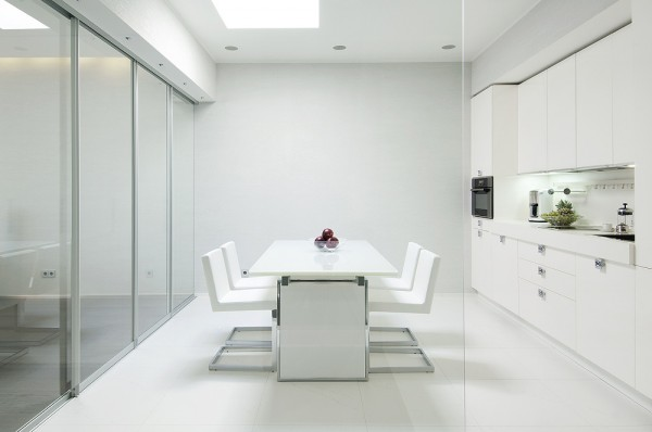 mau-nha-dep-Kitchen-glass-walled-in-white-with-sleek-cabinetry-and-modern-dining-setting-600x398
